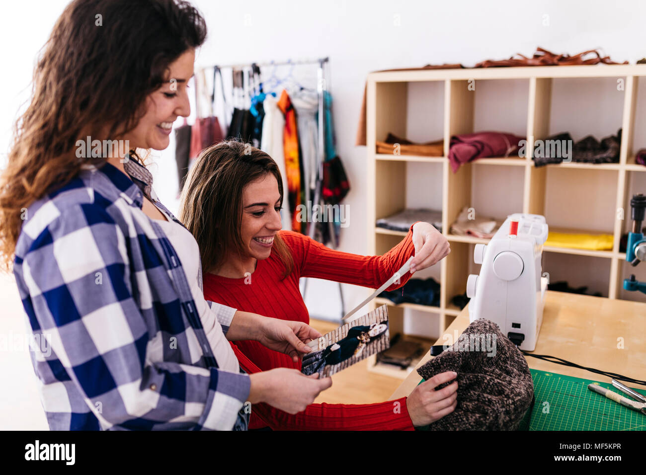 Two happy fashion designers in studio looking at photography - Stock Image