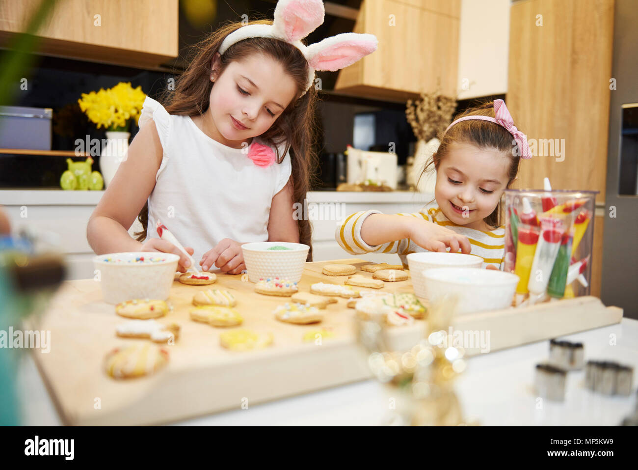 Sisters decorating Easter cookies in kitchen - Stock Image
