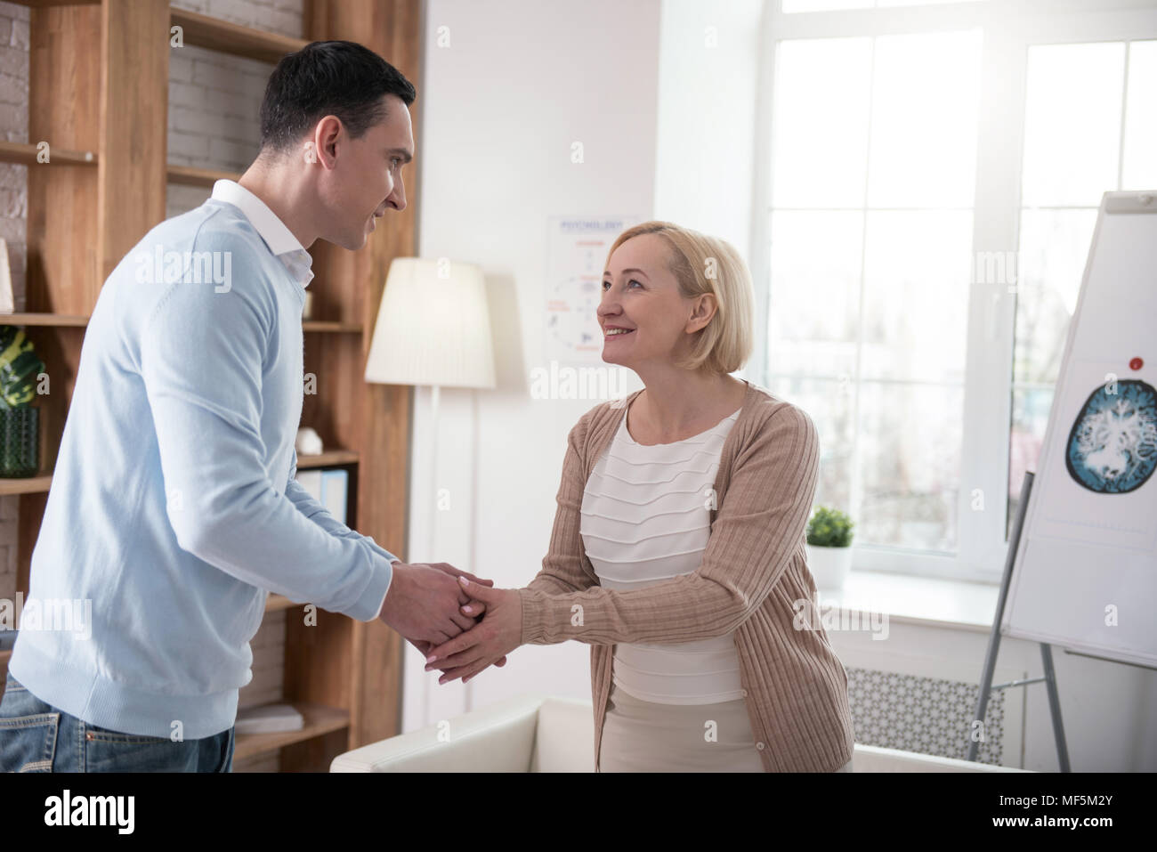 Merry senior woman making acquaintance with man - Stock Image
