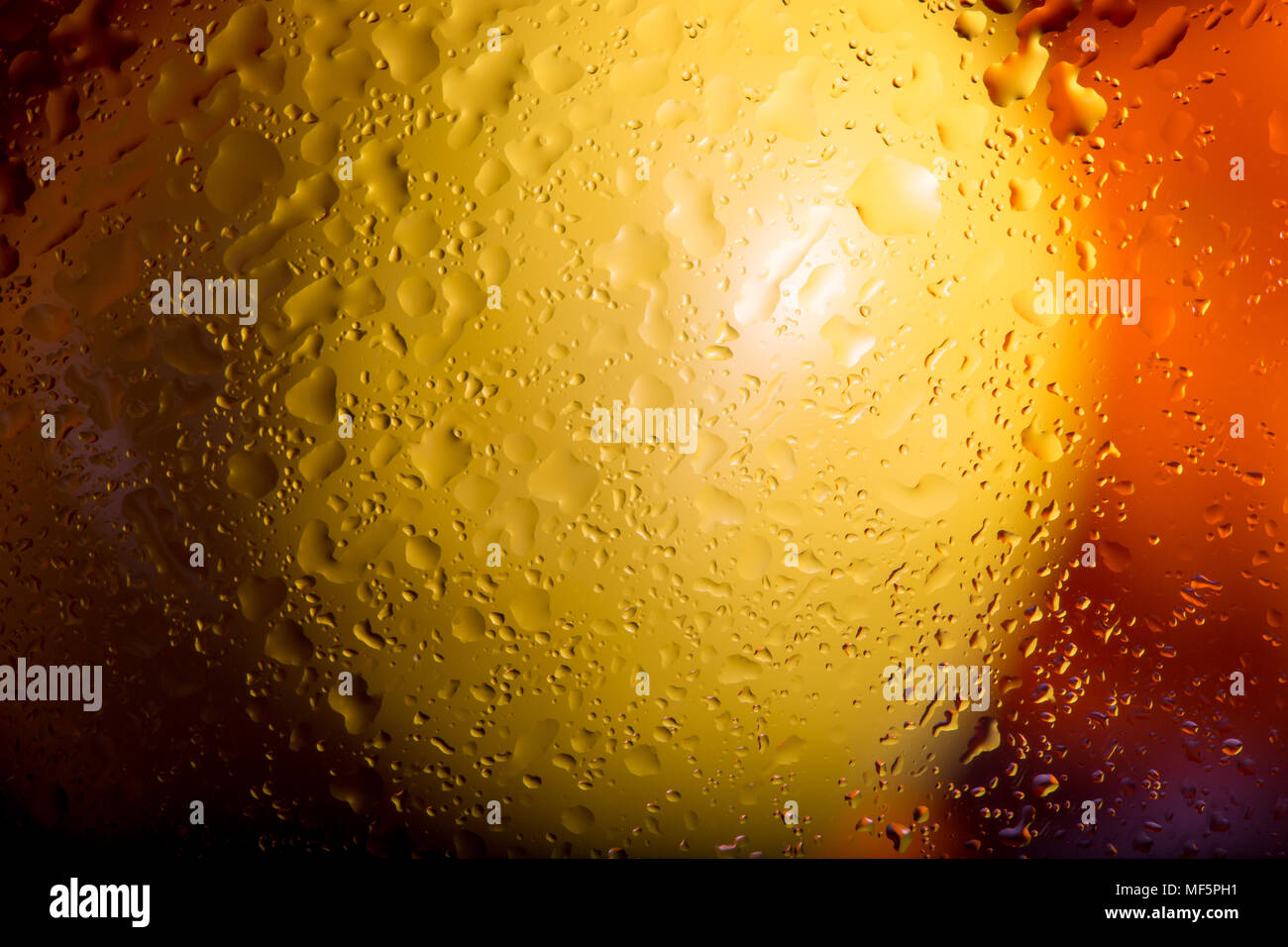 Colourful landscape shot: lemon & orange fresh fruit behind obscured, wet glass. Interesting screen saver design. Abstract / background capture. - Stock Image