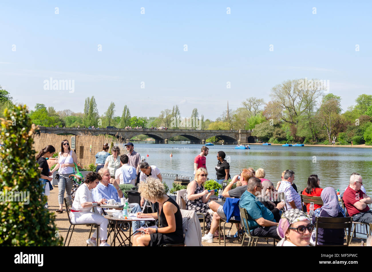 Crowds of people enjoying the spring sunshine at by the Serpentine at Hyde Park, London - Stock Image