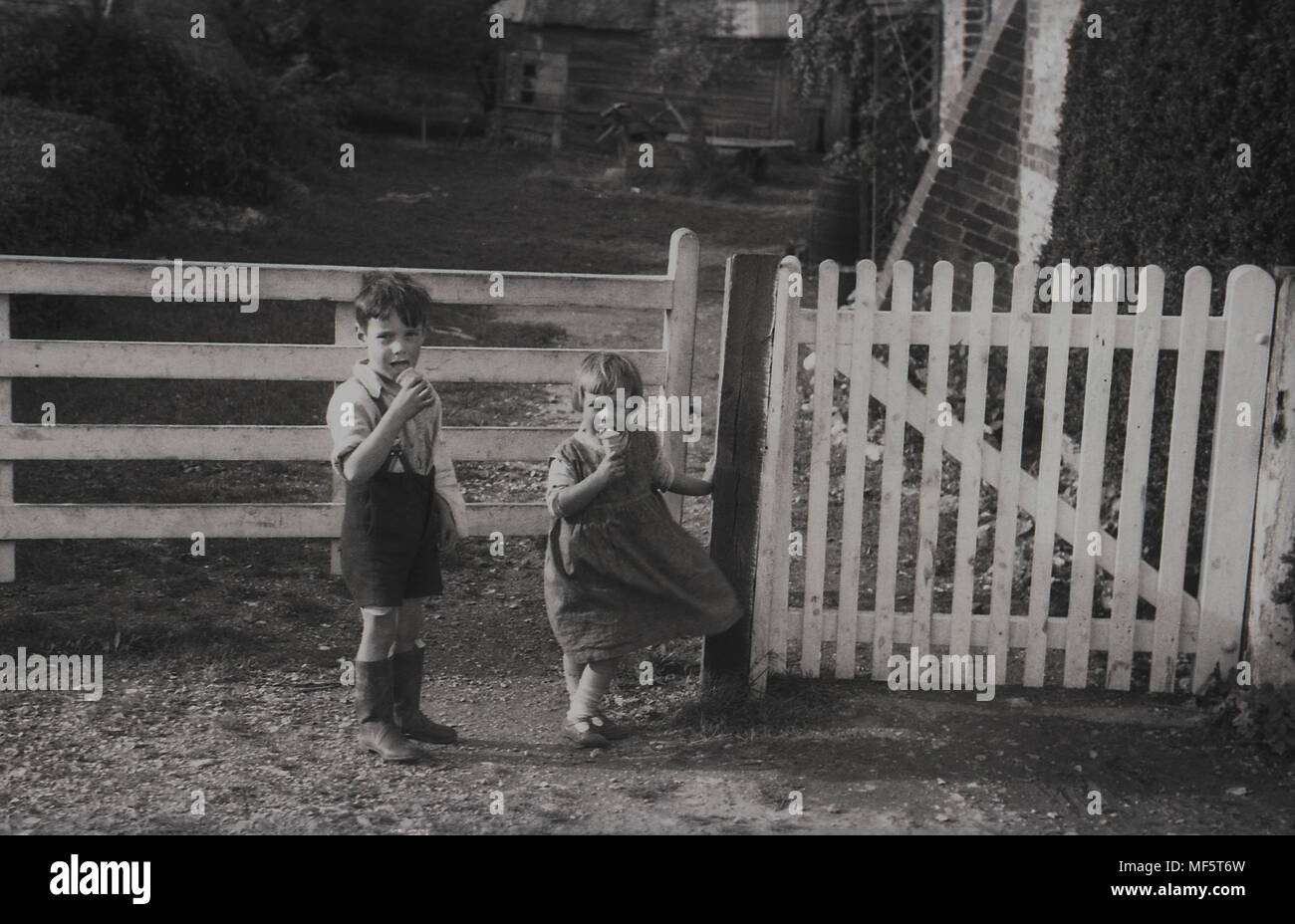 1936, Historical, A Rural Childhood......young Boy And His Younger Sister  Enjoy Their Cornet Ice Creams As They Wait Outside The Gated Entrance To  Their ...