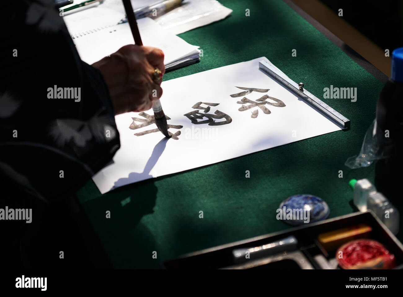 japanese calligraphy, unrecognizable person writing kanji characters (English translation: reserved) with ink brush on paper - Stock Image