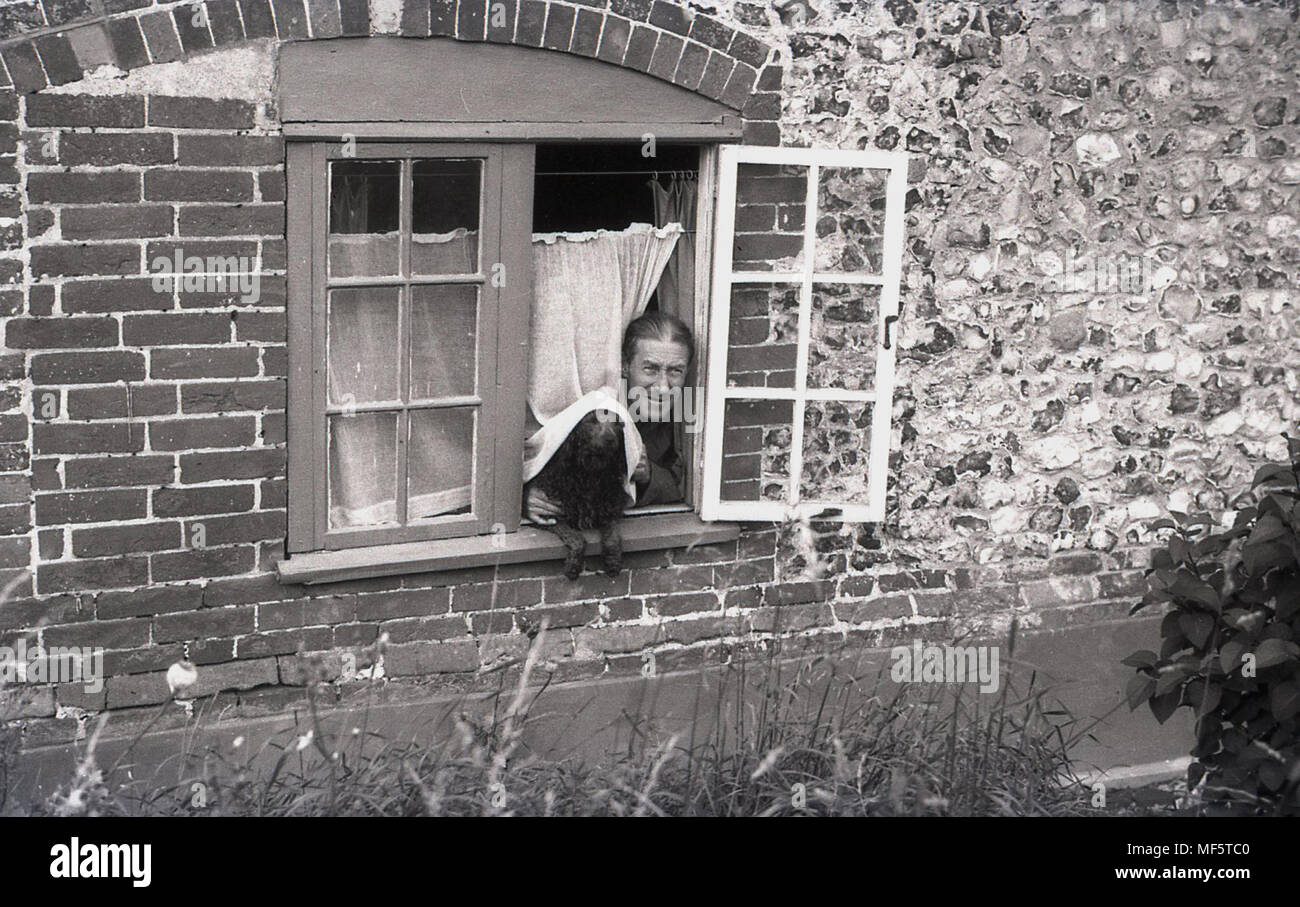 1936, man and his dog peer out of an open cottage window, Hampshire, England, UK. - Stock Image