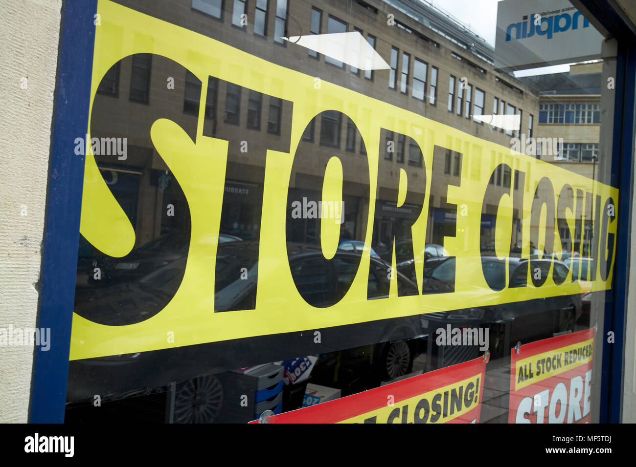 store closing sign in front shop window closing down sale England UK - Stock Image