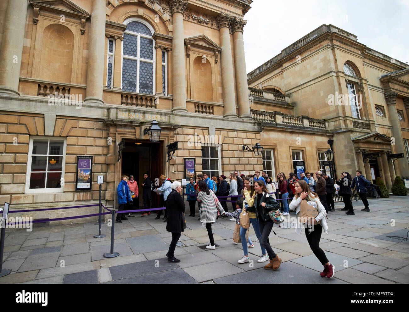 Tourists queue for entry outside the Roman Baths in the centre of historic Bath Somerset England UK - Stock Image