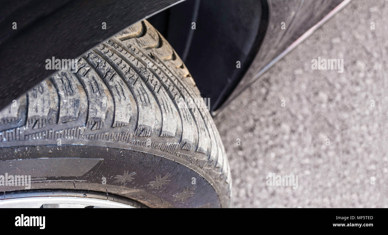 Badly worn out car tire tread and damaged side due to wear and tear or because of poor tracking or alignment of the wheels, dangerous for driving and  - Stock Image
