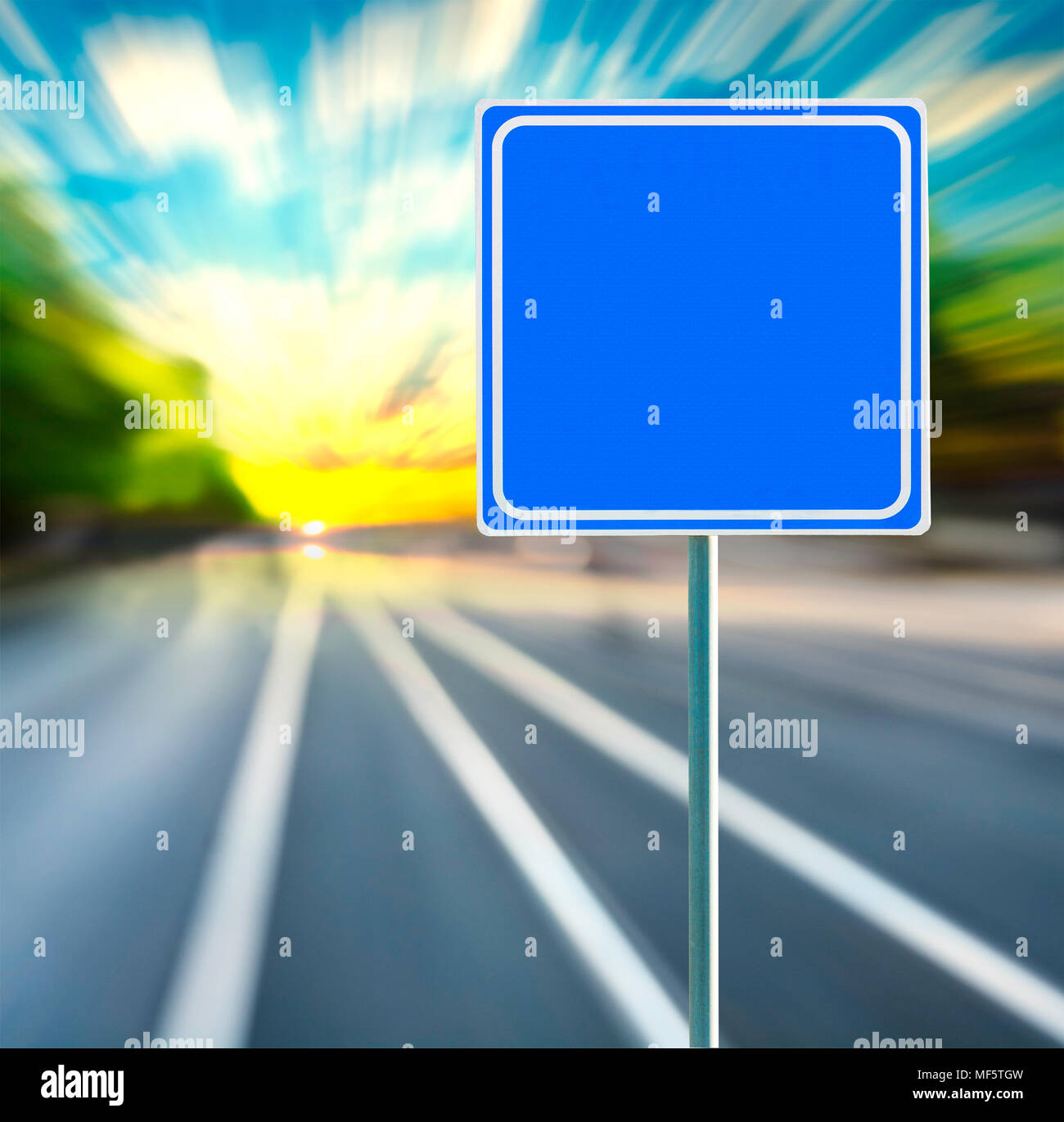 Template, blank, clean blue road sign with blurred speedy background in sunset. Copy space. Stock Photo