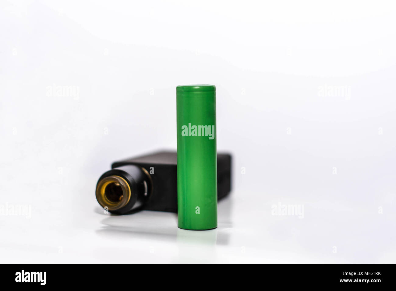 personal vaporizer with battery and q juice or e liquid, green battery and black e ciggaretes with liquid isolated in white background - Stock Image