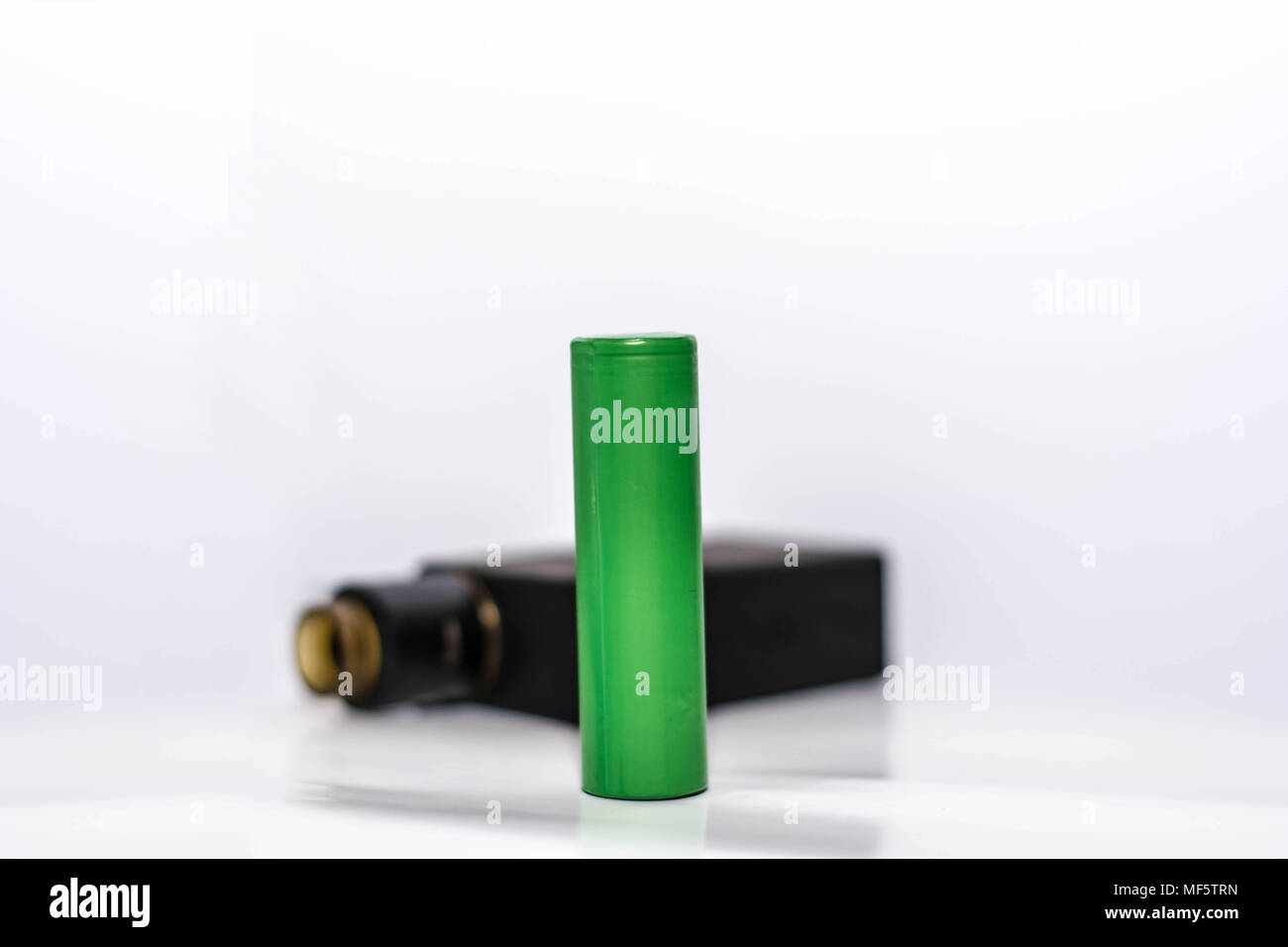 green battery with personal vaporizer in black colour isolated with white background - Stock Image