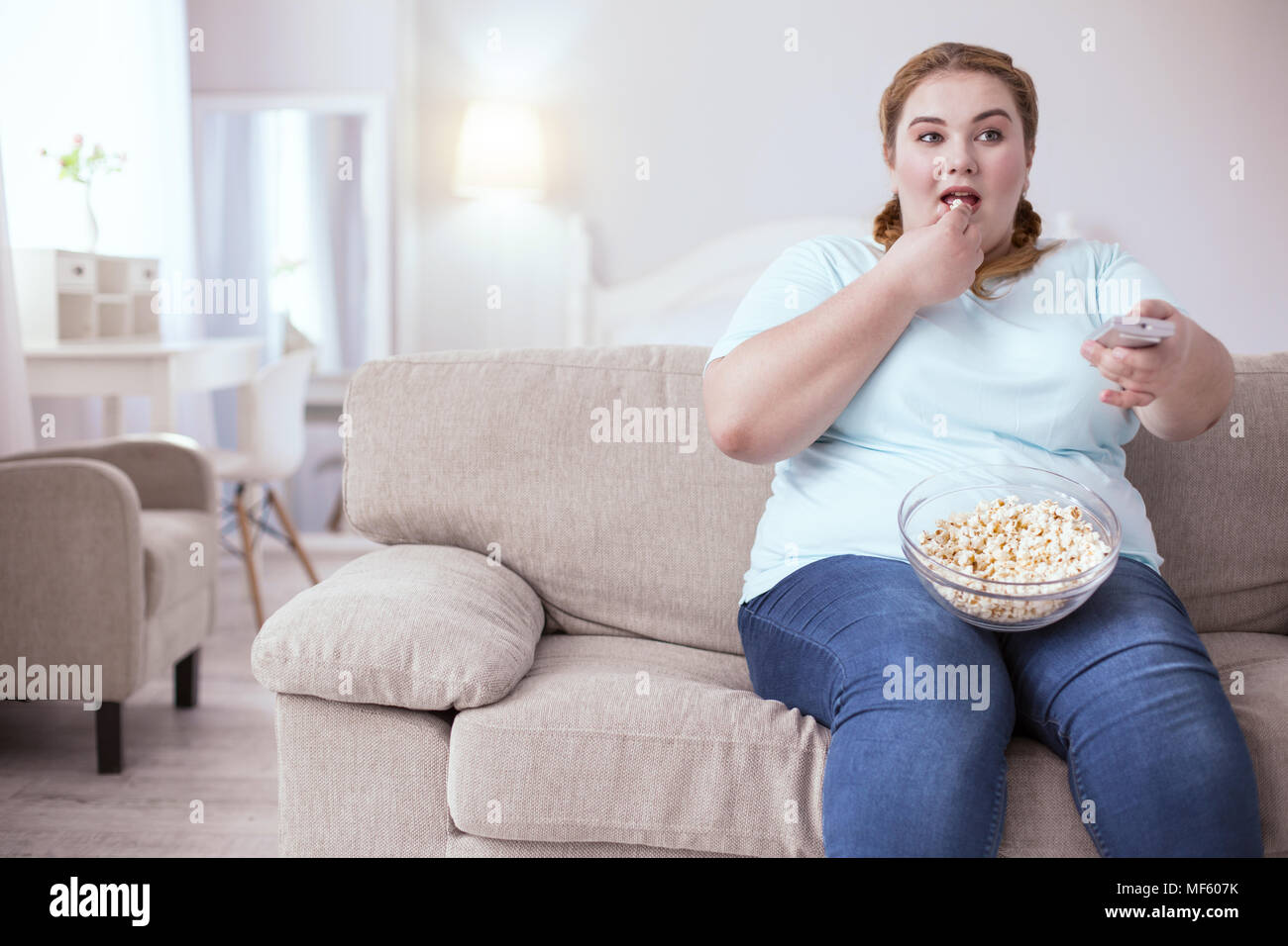 Thoughtful plump woman watching television - Stock Image