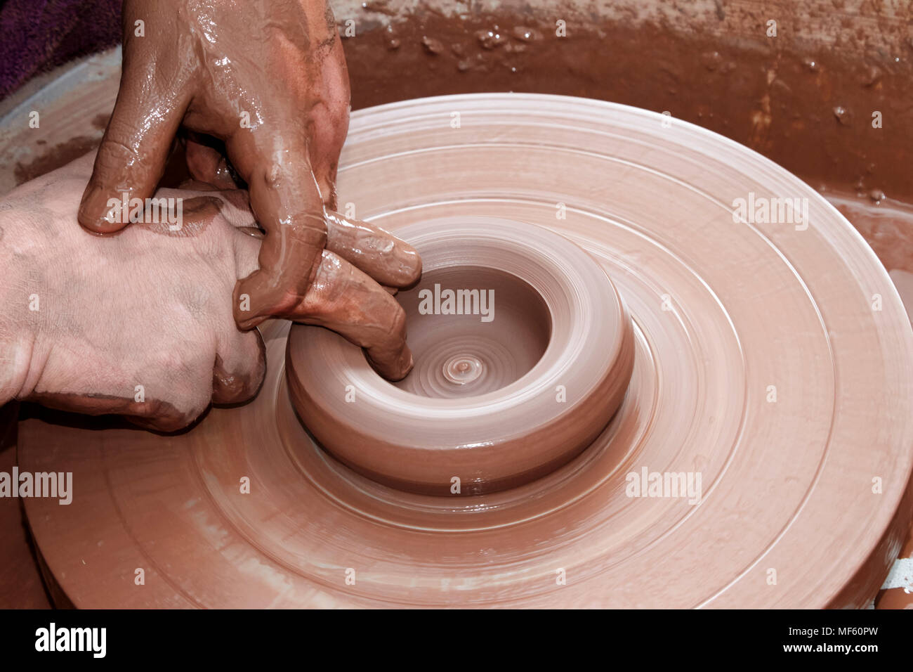 potter working clay on a spinning wheel in the uk Stock Photo