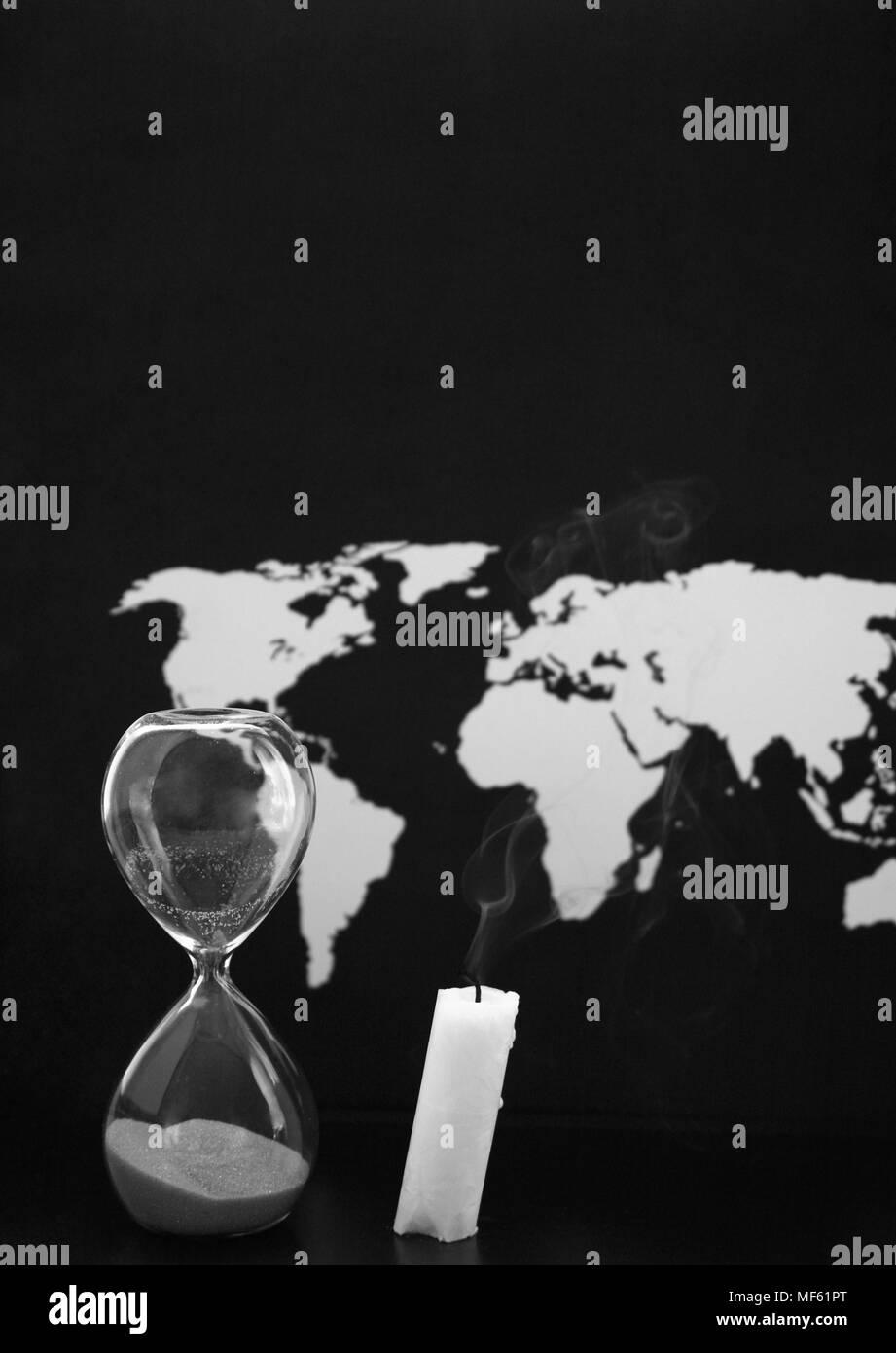 Monochrome image, world map, sandglass and burnt candle, black background - Stock Image