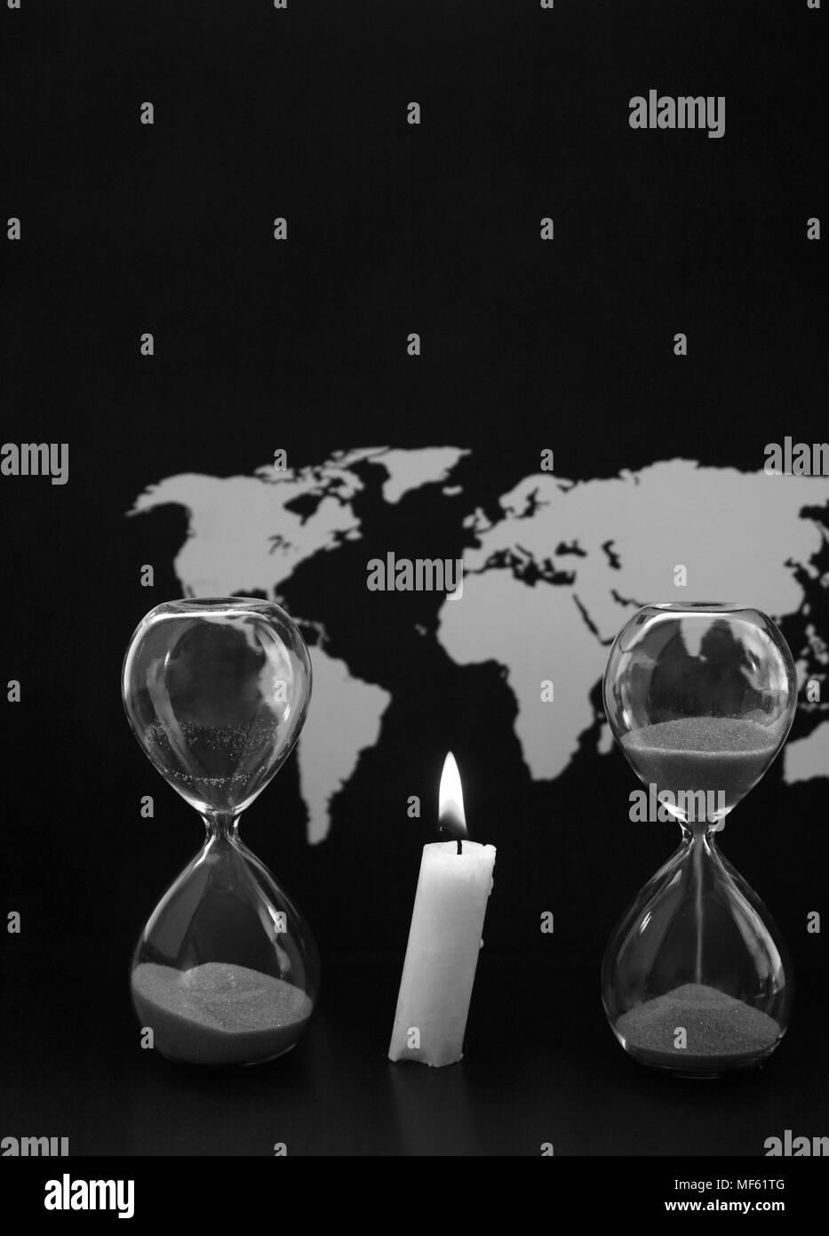 Monochrome image, world map, sandglasses and burning candle, black background - Stock Image