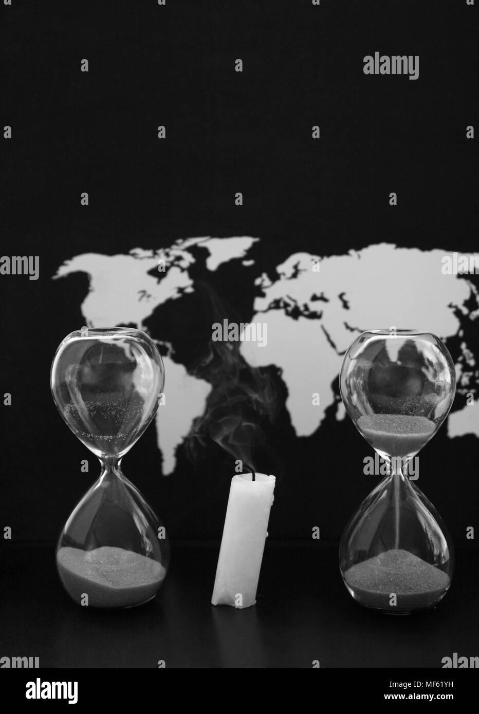 Monochrome image, world map, sandglasses and burnt candle, black background - Stock Image