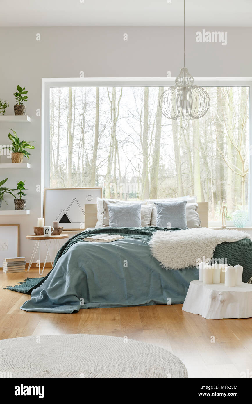 Lamp Above Bed With Green Bedding Near Candles In Bright Bedroom Interior  With Plants And Window