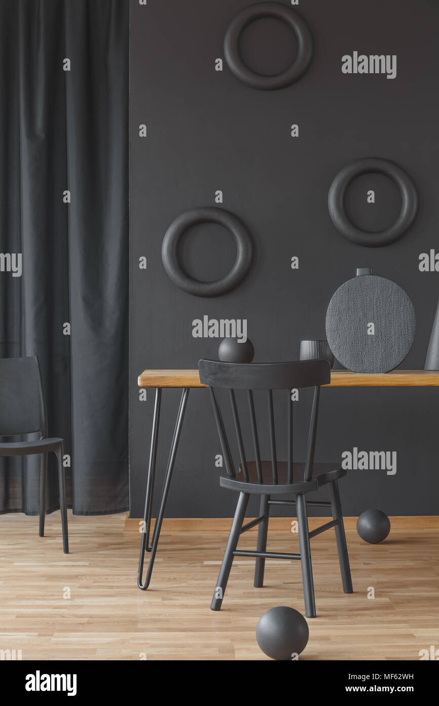 Black round and circular decorations in dark, monochromatic dining room interior with wooden furniture - Stock Image