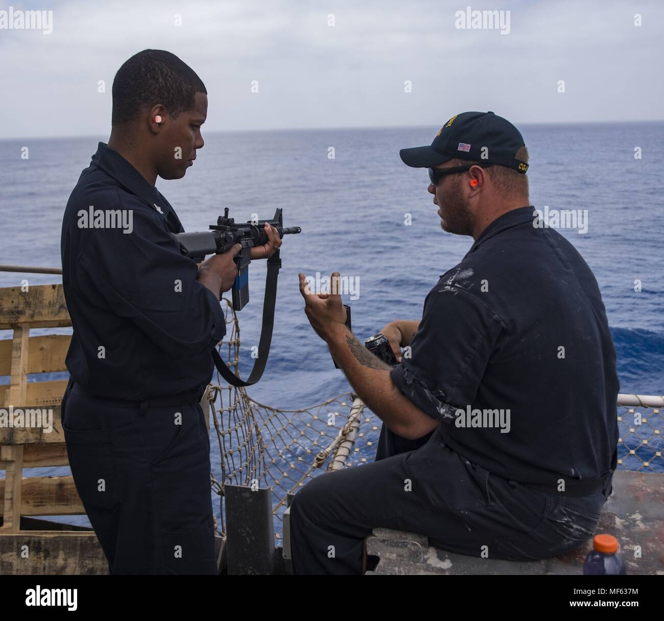 180418-N-DO281-0163 MEDITERRANEAN SEA (April 18, 2018) Gunner's Mate 3rd Class Tyler Aughtman, right, gives training to Cryptologic Technician (Technical) 2nd Class Alexis Grassettesantos, left, on the proper way to fire a M-16 rifle during a live-fire exercise aboard the guided-missile cruiser USS Monterey (CG 61), April 18, 2018. Monterey, home-ported in Norfolk, Virginia, is conducting operations in the U.S. 6th Fleet area of operations in support of U.S. national security interest in Europe. (U.S. Navy photo by Mass Communication Specialist Seaman Trey Fowler). () Stock Photo