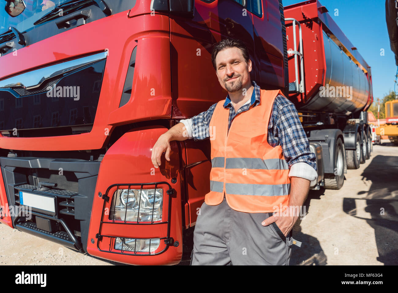 Truck driver in front of his freight forward lorry - Stock Image