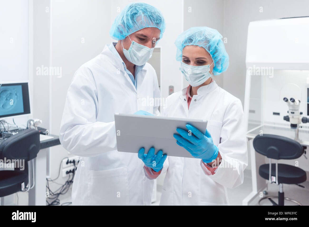Two scientists working together in lab looking at data - Stock Image