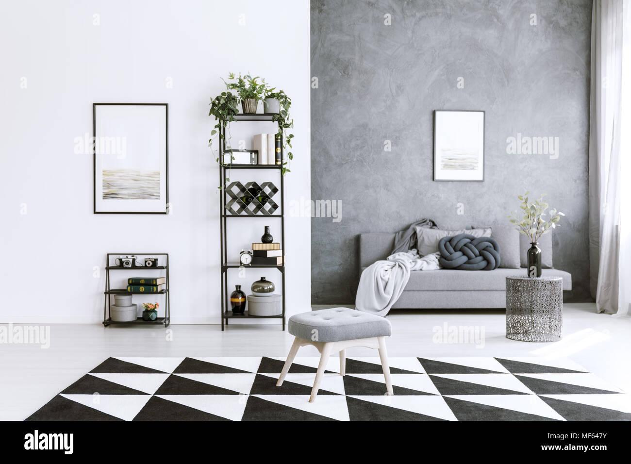 Grey living room interior with asymmetrical carpet, metal shelf ...
