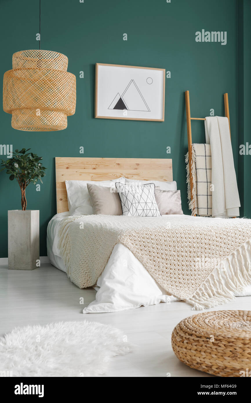 Pouf And White Fur On The Floor Near Bed With Knit Blanket In Emerald Green Bedroom Interior With Plant And Poster Stock Photo Alamy