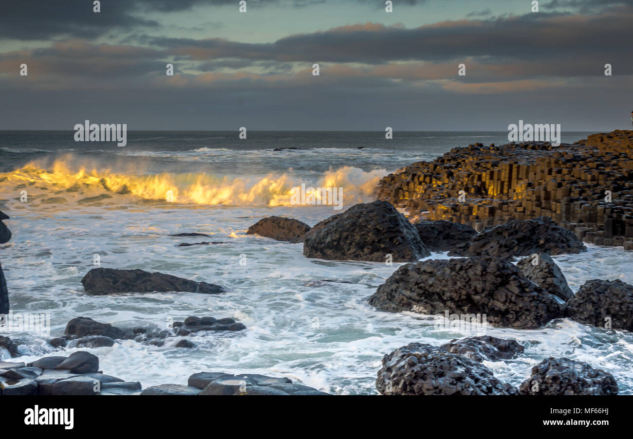 The waves crashing over the hexagonal rock formation at the Giant Causeway just before sunset, Northern Ireland, UK - Stock Image