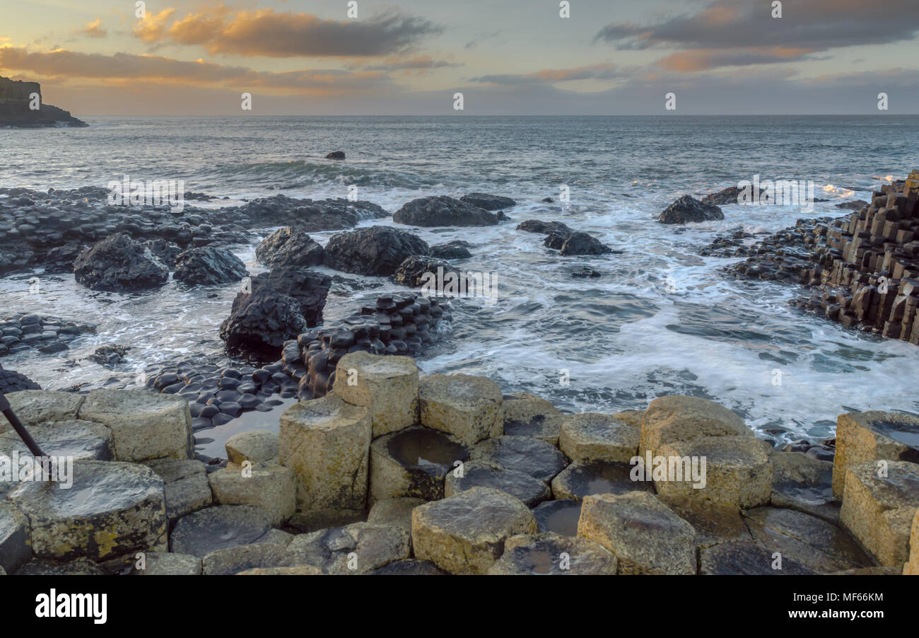 Giant's Causeway, North Ireland, UK during winters. The fierce waves batter the iconic coastline of North Ireland. In a distance the sky is lit with s - Stock Image