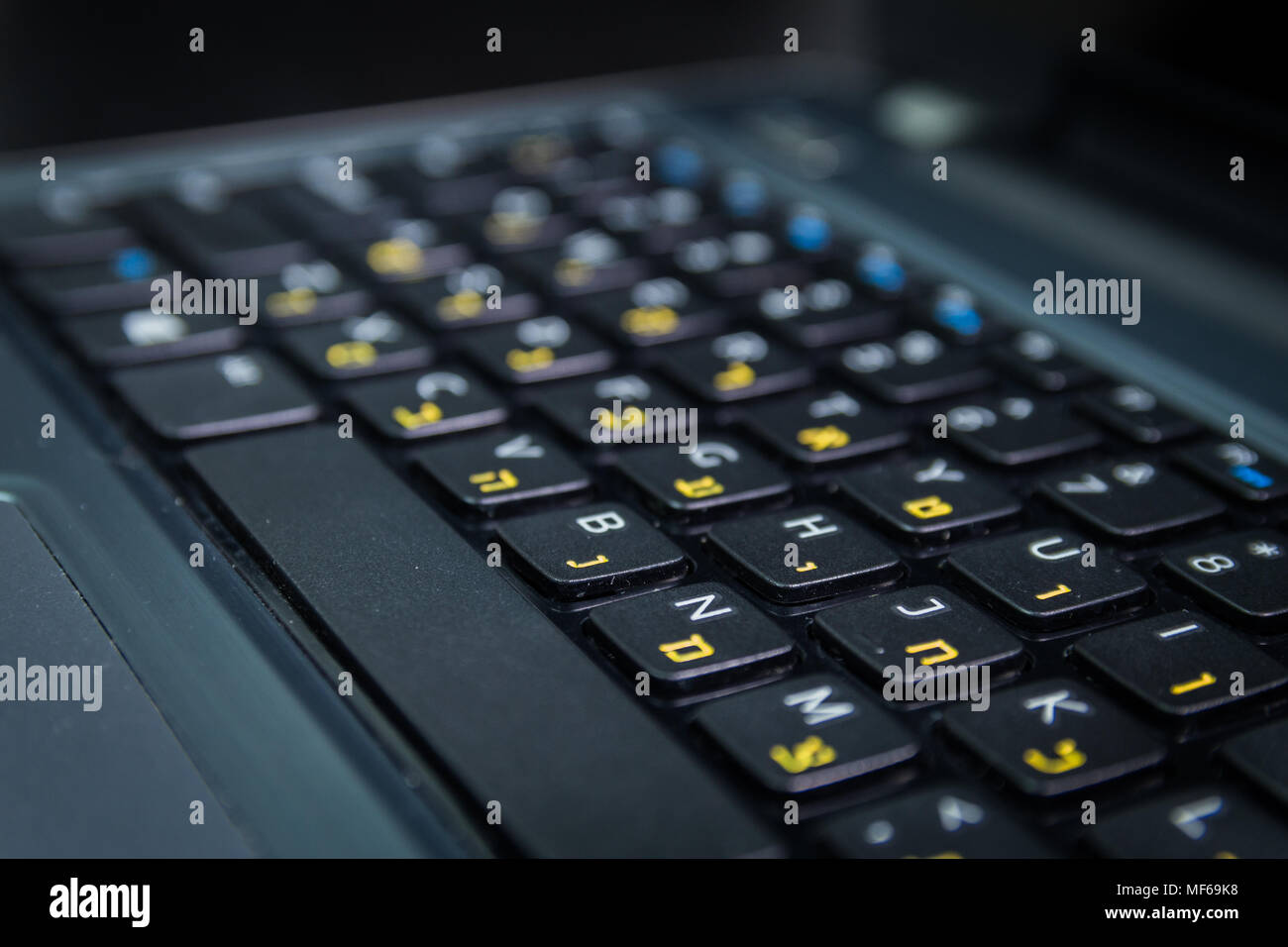 Keyboard with letters in Hebrew and English - Laptop keyboard - Close up - Dark atmosphere - Stock Image