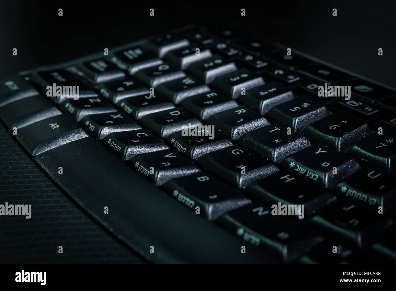 Keyboard with letters in Hebrew and English - Wireless keyboard - Close up - Dark atmosphere - Stock Image