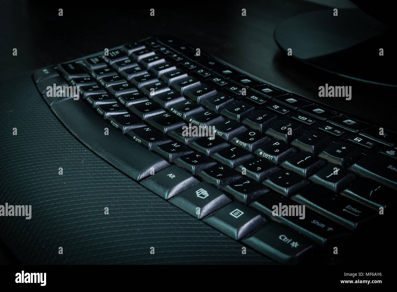 Keyboard with letters in Hebrew and English - Wireless keyboard - Dark atmosphere - Stock Image