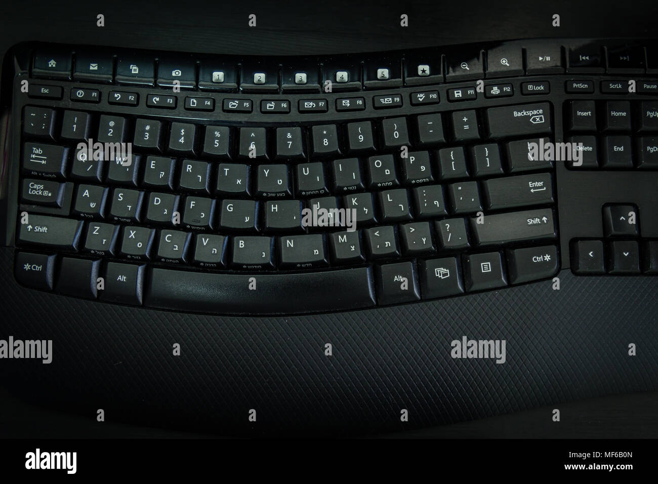 Keyboard with letters in Hebrew and English - Wireless keyboard - Top View -  Dark atmosphere - Stock Image