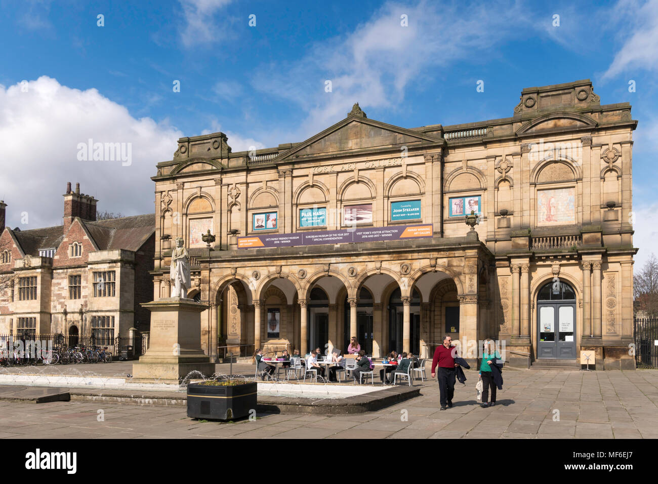 A couple leave York Art Gallery while a party of schoolchildren sit near the entrance, Exhibition Square, York, Yorkshire, England, UK - Stock Image