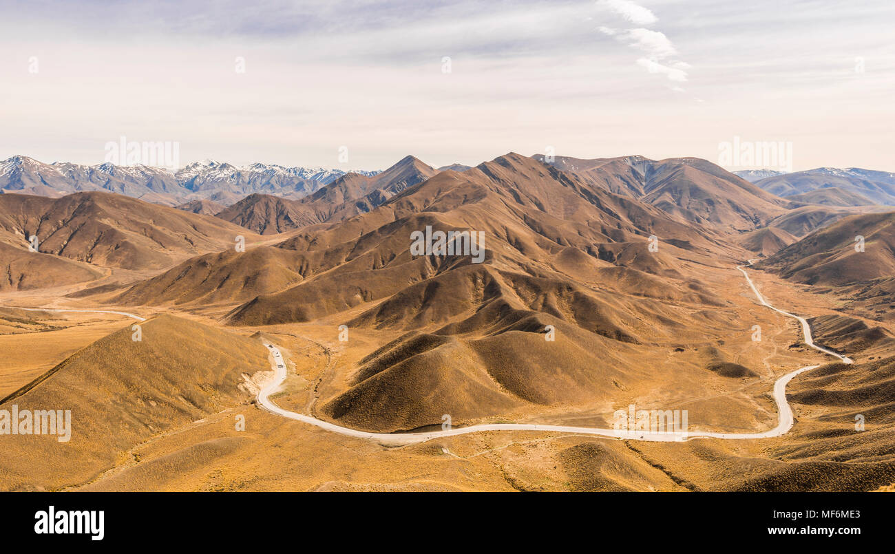 Stark mountain landscape with mountain road, Lindis Pass, Southern Alps, Otago, Southland, New Zealand - Stock Image