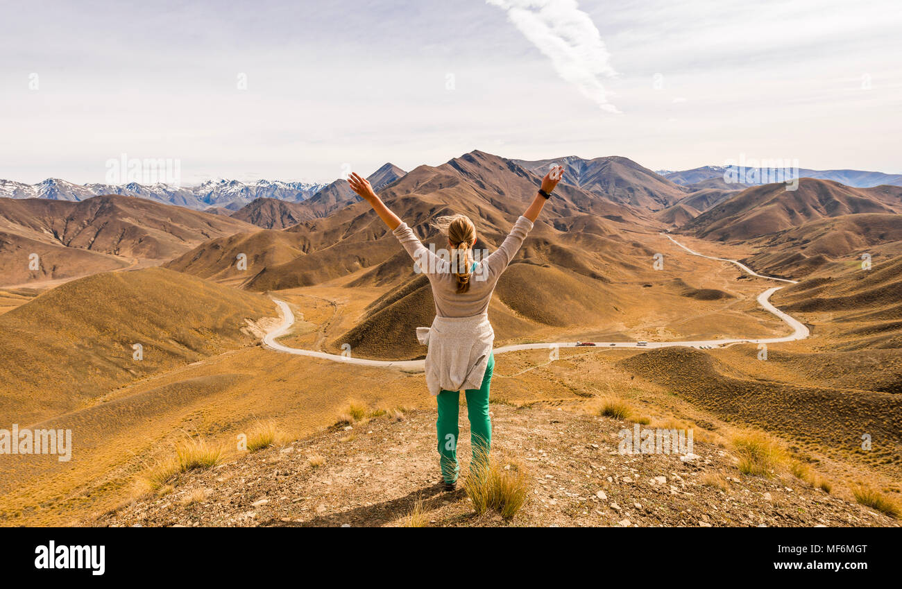 Woman looking at stark mountain landscape with mountain road, Lindis Pass, Southern Alps, Otago, Southland, New Zealand - Stock Image