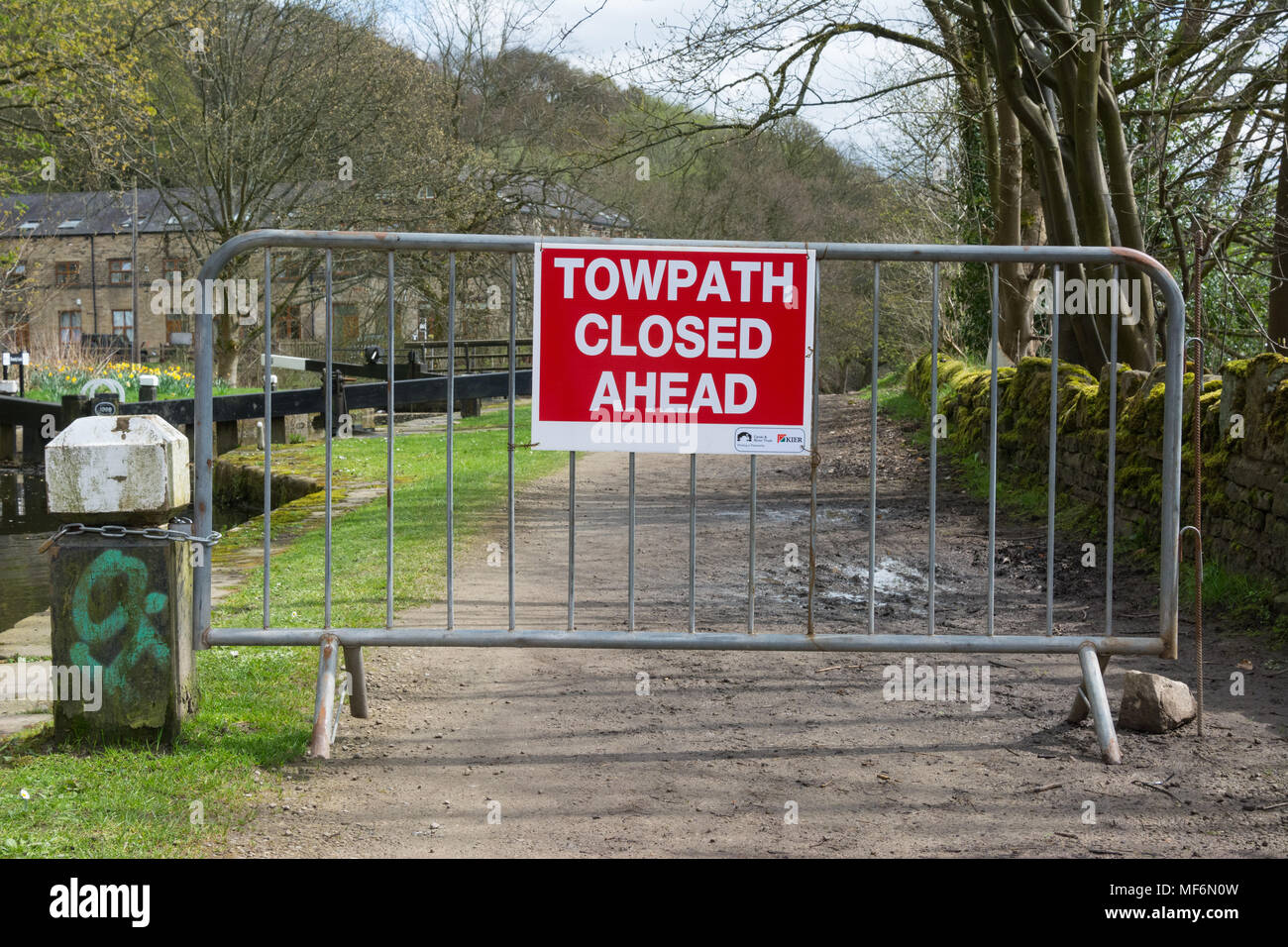 A sign on a barrier placed across the towpath of the Rochdale Canal at Hebden Bridge says 'Towpath Closed Ahead' as work is done to mend the towpath. - Stock Image