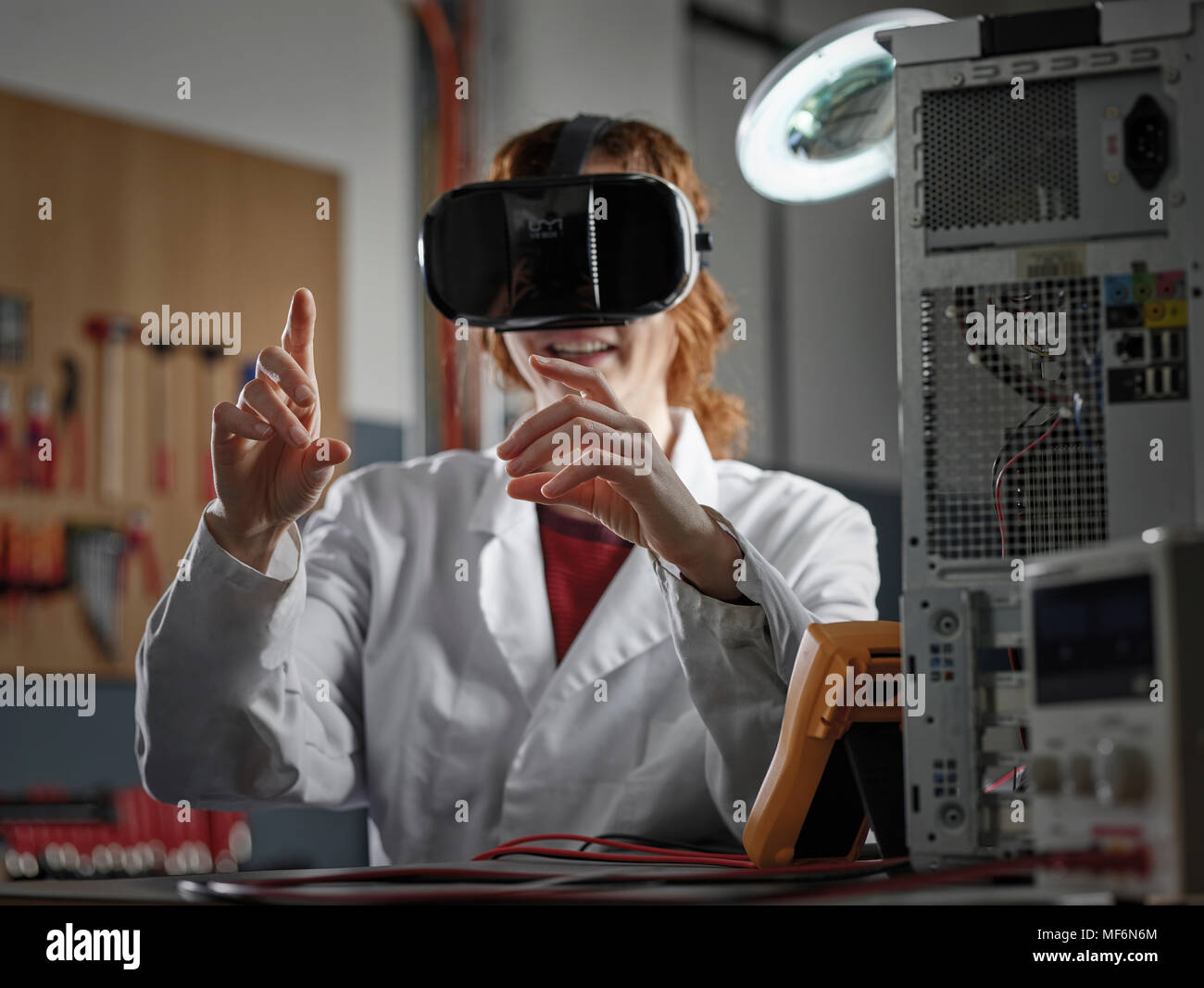 Woman with VR goggles and lab coat sitting in an electronics laboratory, Austria - Stock Image