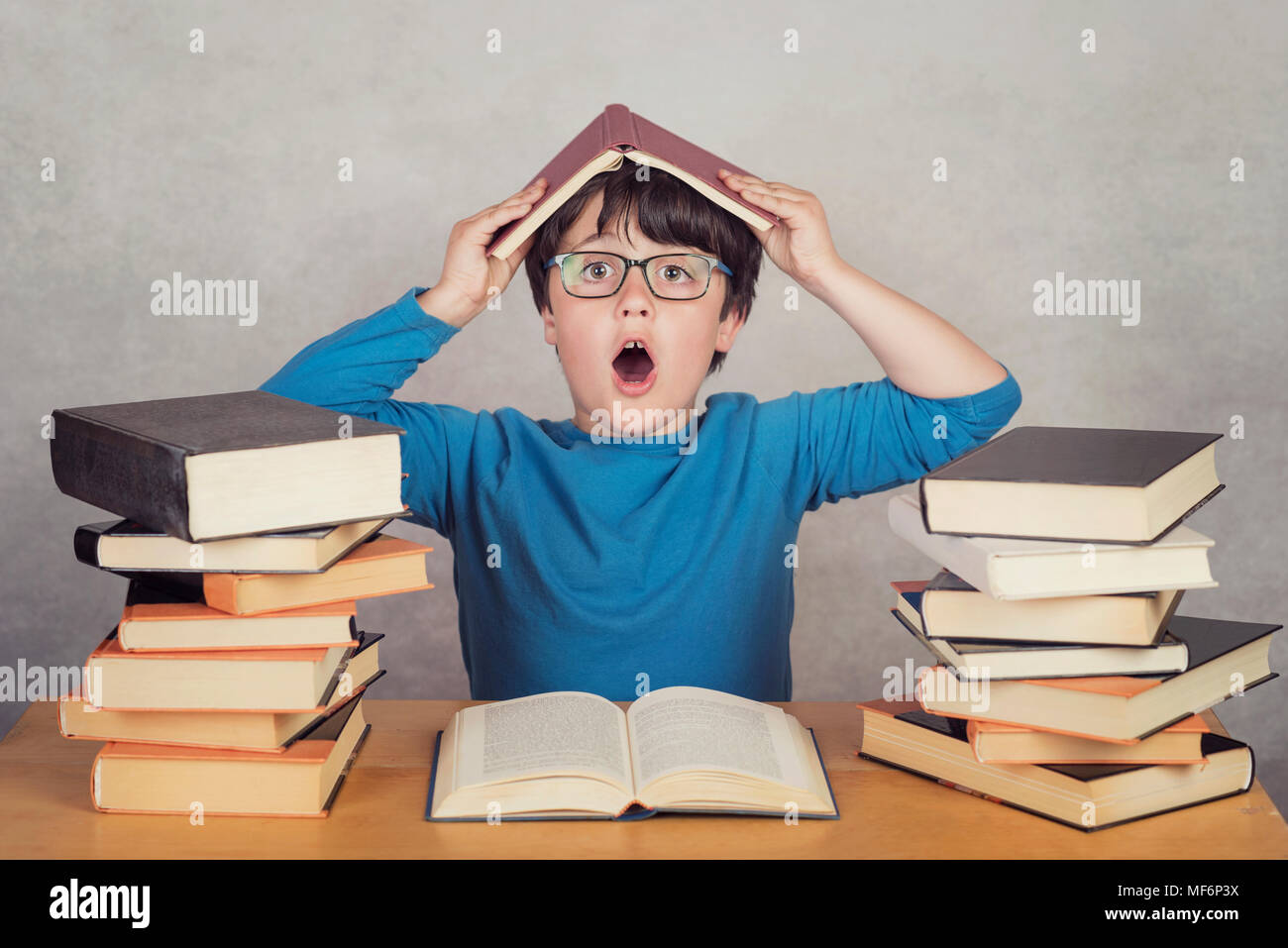 surprised boy with books on a table - Stock Image