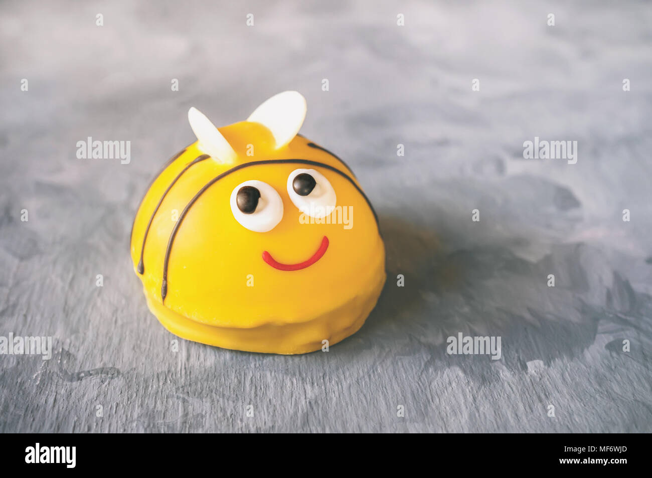 Traditional marzipan sweets, confectionery, cakes. A cake in the shape of a bee. Copy spase. Stock Photo