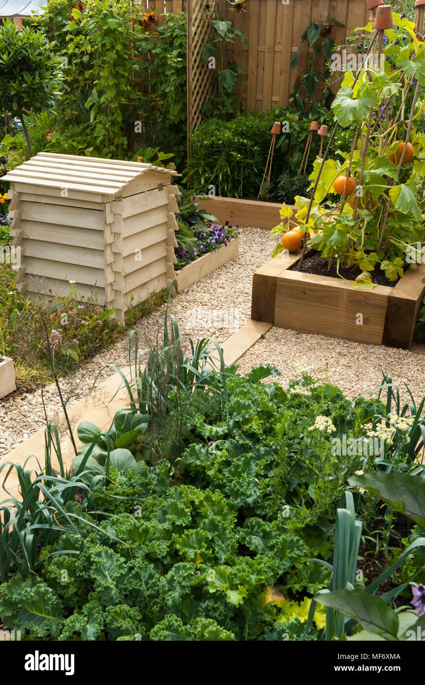 Beehive & raised timber beds with mixed vegetable crops (companion planting) growing in kitchen garden - RHS Flower Show, Tatton Park, England, UK. - Stock Image
