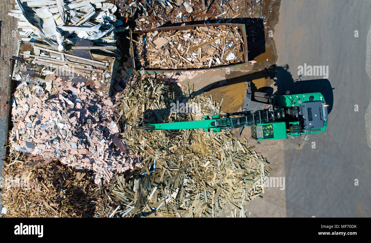 Aerial photo of a crane with a huge claw in front of a wood scrap heap - Stock Image