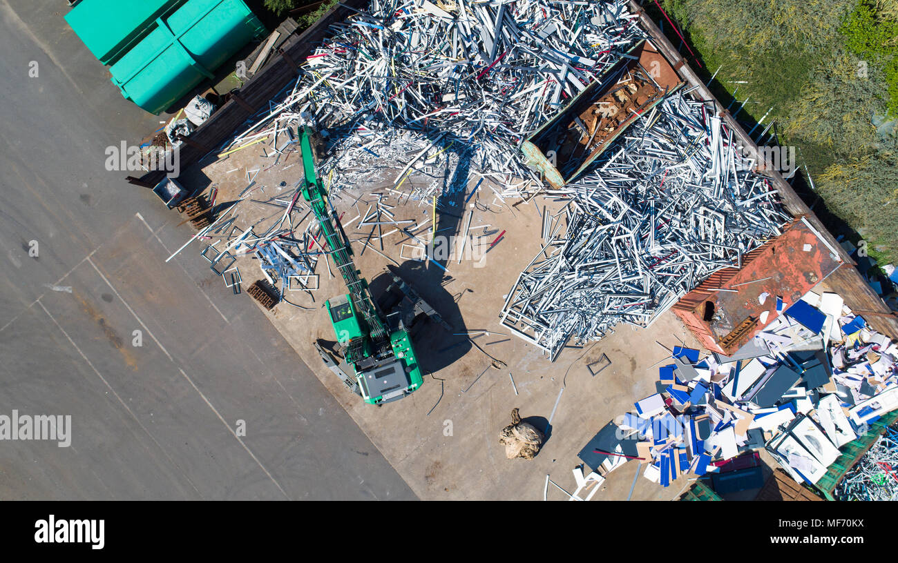 Aerial photo of a crane with a huge claw in front of a steel scrap heap - Stock Image