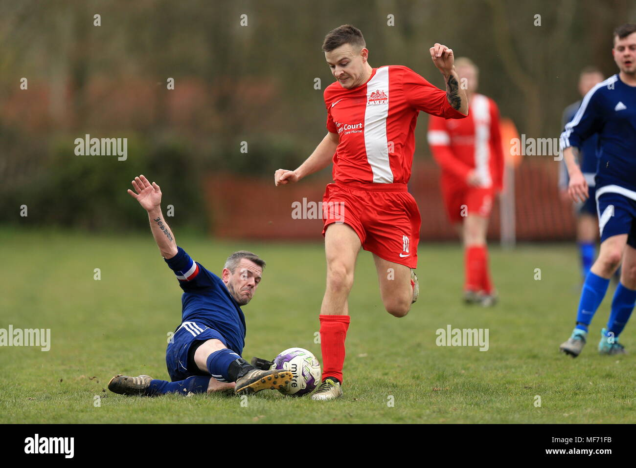 A Blacksmith Arms FC player challenges for the ball on a sunday morning game against Charlwood Village Reserves in the Redhill and District League - Stock Image