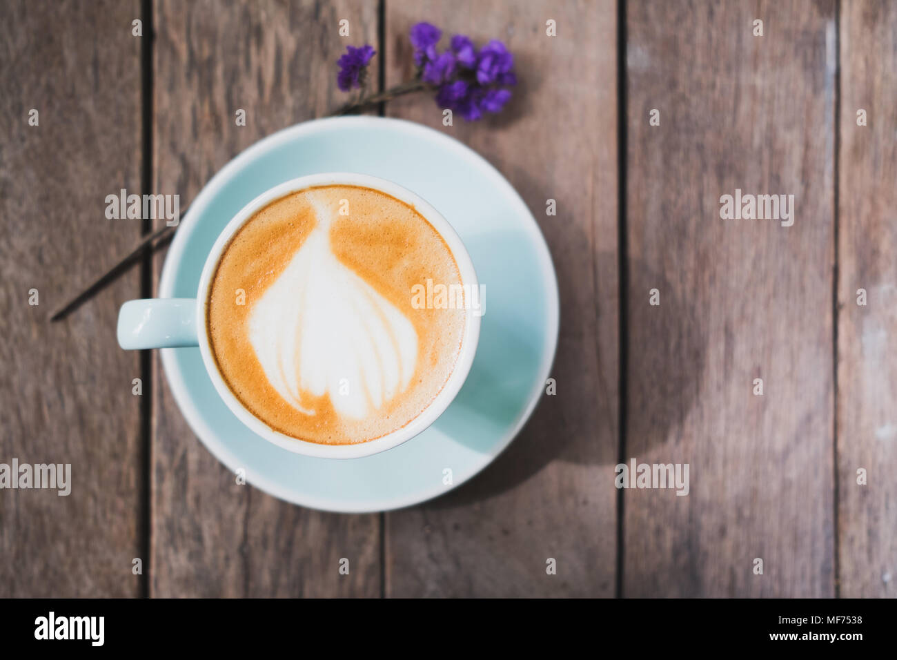 Top view of hot coffee in green cup with latte art on wooden plank table with forget me not flower,Food and drink concept,vintage filter Stock Photo