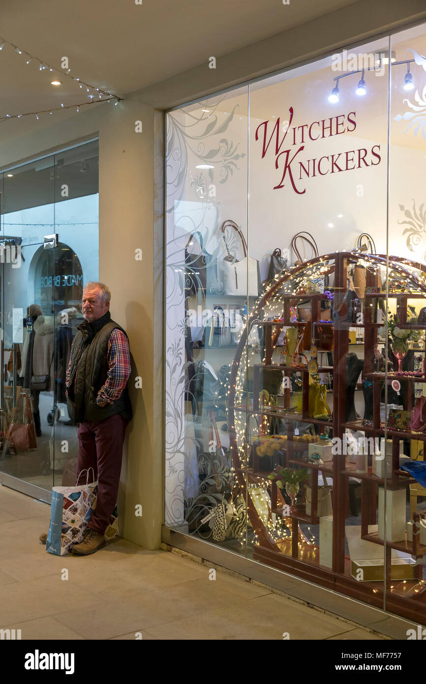 Man looking at the camera waiting outside a shop called Witches Knickers in The Corn Hall shopping arcade, Cirencester, Gloucestershire, England, UK - Stock Image