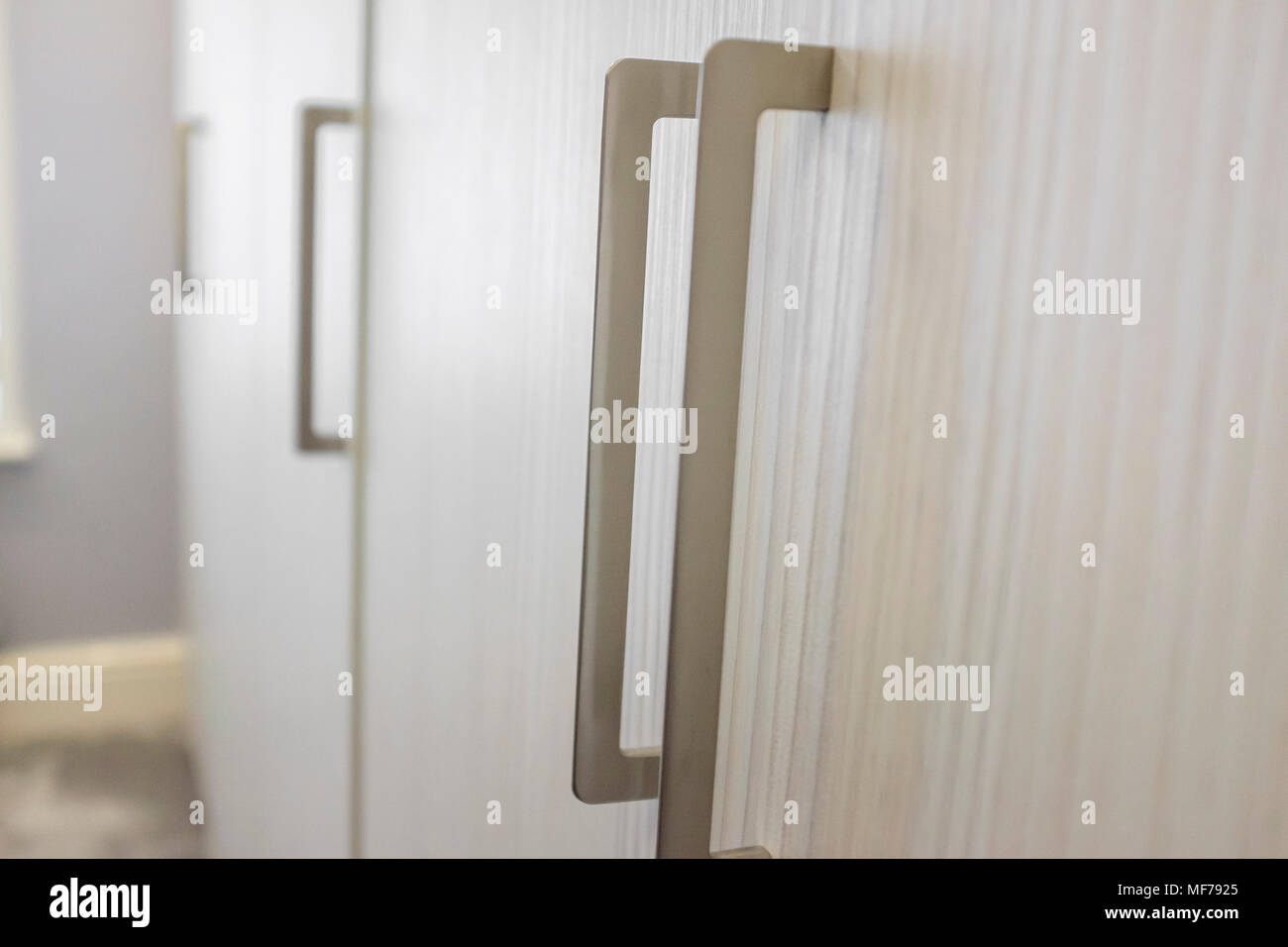 Silver handles on a modern fitted wardrobe. - Stock Image