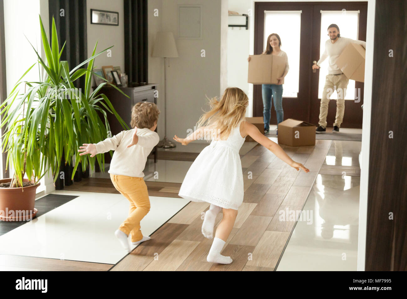 Rear view at kids running to parents on moving day - Stock Image