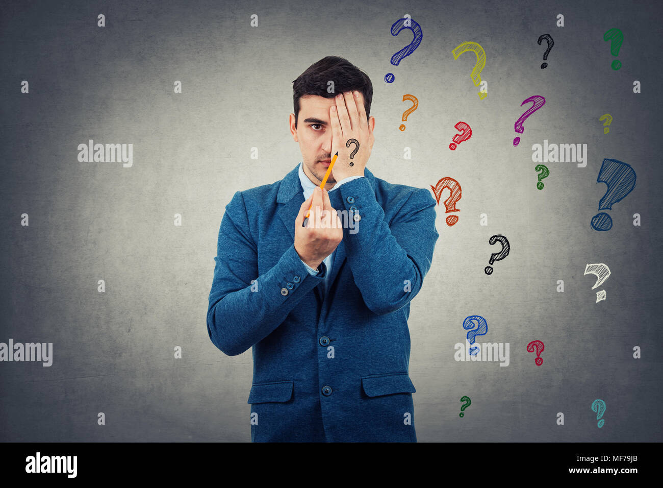 Portrait of young man hiding half face with his palm trying to draw new identity. Half face with sad, angry emotion and another one is unknown. Colorf - Stock Image