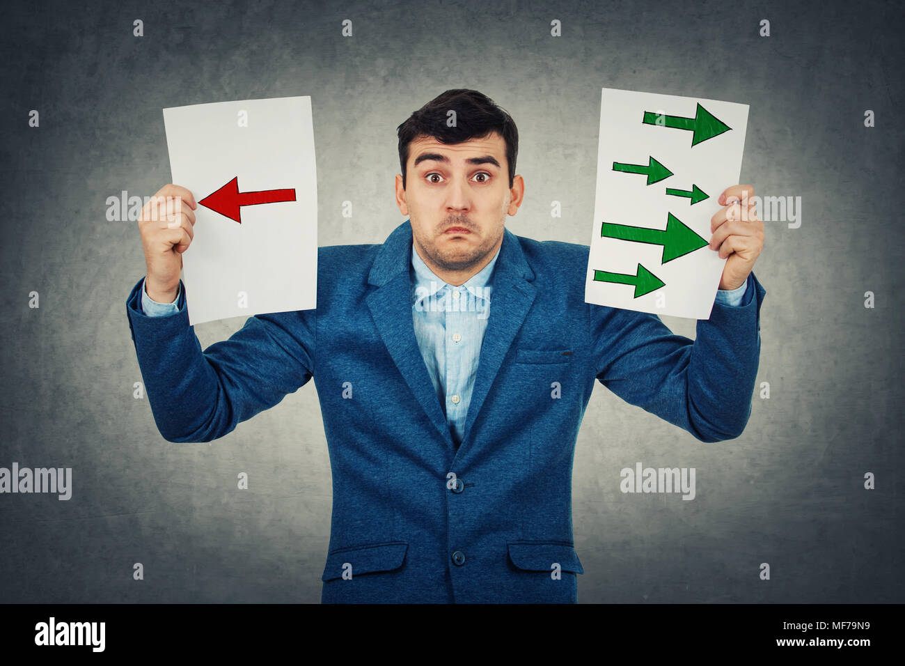 Confused young businessman holding two sheets with drawn arrows poinded to the left and right side. Undecided boy try to choose between two directions - Stock Image
