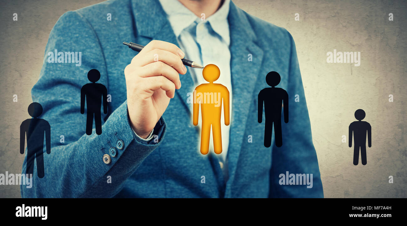 Businessman drawing small people icons, one of them is different colored, yellow among black. Employee choosing, group leadership concept. Select the  Stock Photo